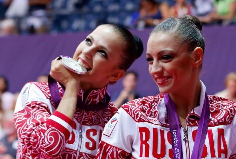Silver medallist Russia's Daria Dmitrieva celebrates with gold medallist compatriot Evgeniya Kanaeva in the individual all-around gymnastics final victory ceremony at the Wembley Arena